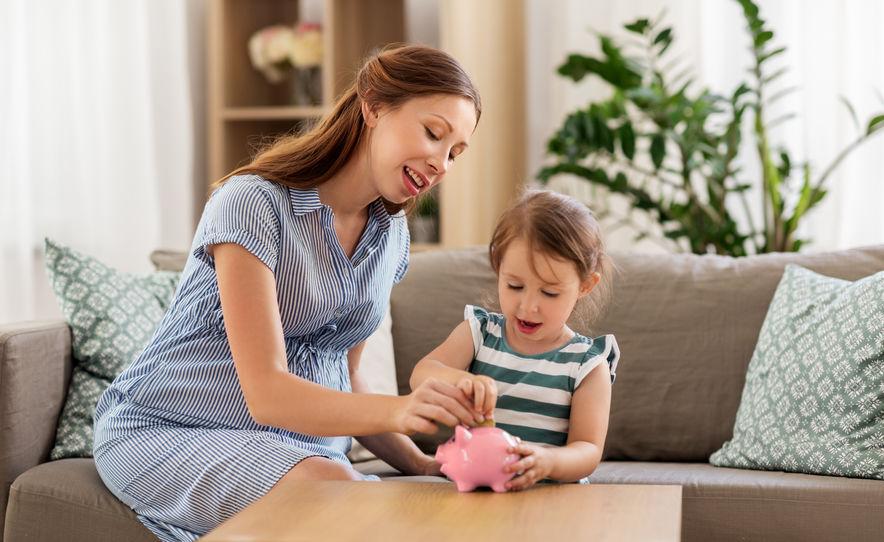 Frau mit Kind spart Geld im Sparschwein - so sparen Frauen