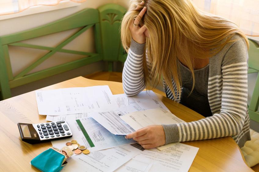 Frau mit Geldbeutel, Taschenrechner und Papieren - Strategie zum Schuldenabbau