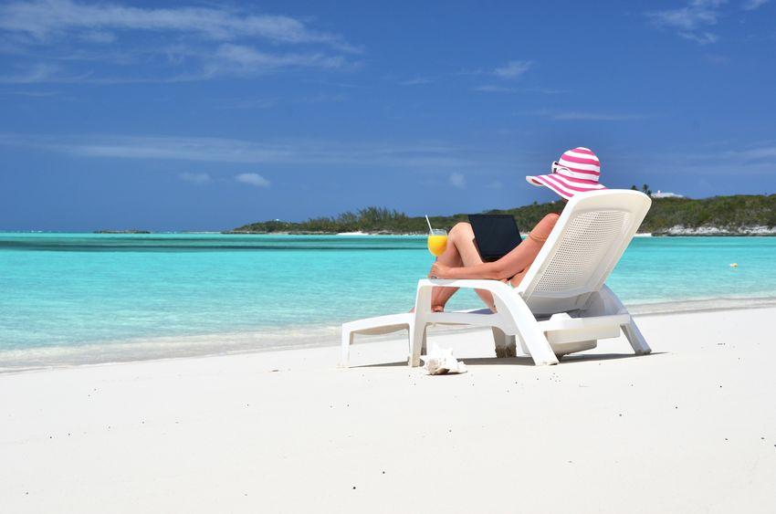 Frau am Strand mit Computer - passives Einkommen generieren